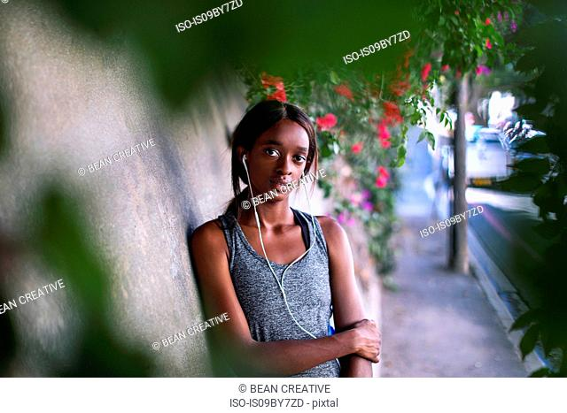 Young female runner listening to earphones leaning against city sidewalk wall, waist up portrait