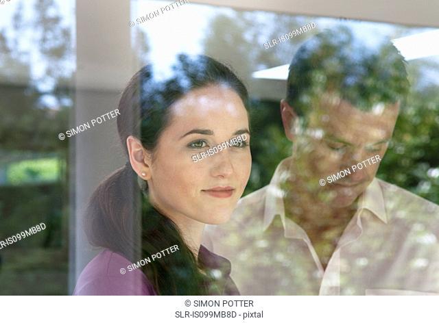 Woman looking through window, man looking down