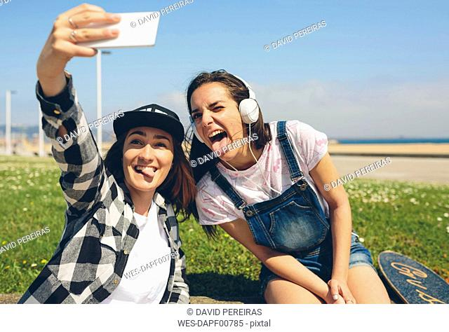 Portrait of two young women taking selfie with smartphone