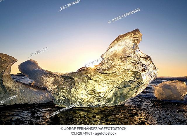 Sunrise of a very clear day over the pieces of ice shed from the Jokullsarlon glaciers pushed to the seashore at the Jokulsarlon Ice Beach