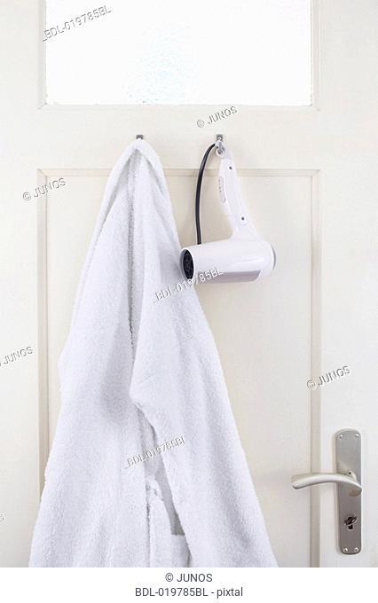 bathrobe and hair dryer hanging on bathroom door