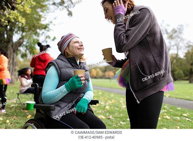 Woman in wheelchair talking to friend in park