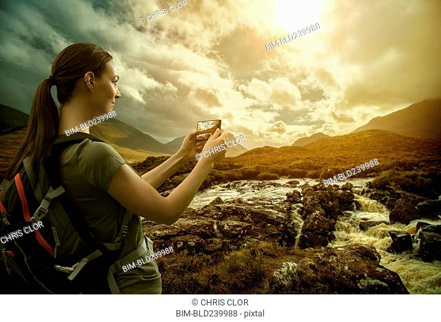 Caucasian woman photographing mountain river with cell phone