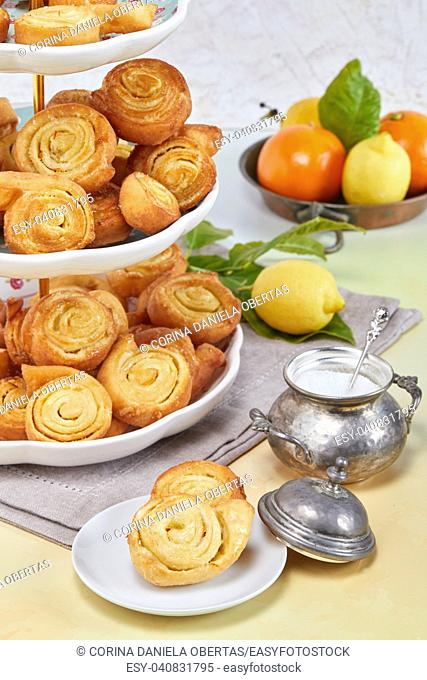 Closeup of Italian pinwheel orange pastries, typical sweets made during the carnival period from fried puff pastry flavored with orange zest and honey