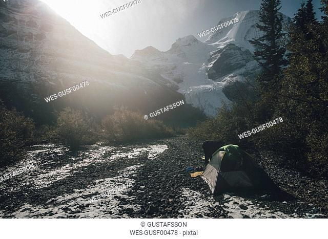 Canada, British Columbia, Mount Robson Provincial Park, man with tent at Berg Glacier