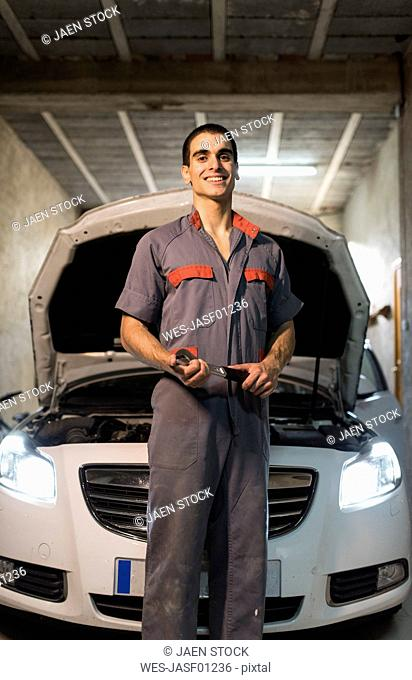 Portrait of smiling mechanic in front of car in a garage