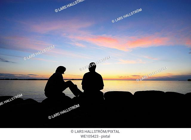 Silhouette of a couple by a lake at sunset, Sweden
