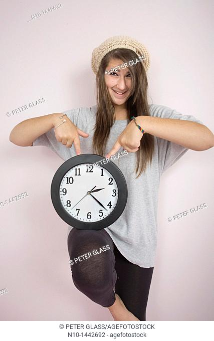 Teen girl holding a wall clock