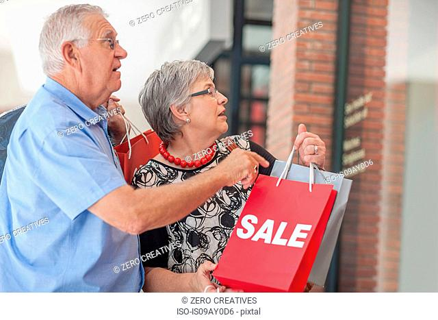 Mature couple carrying shopping bags, looking in shop window