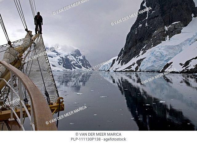 Sailing ship with man on bowsprit looking into the Lemaire Channel / Kodak Gap, Antarctica