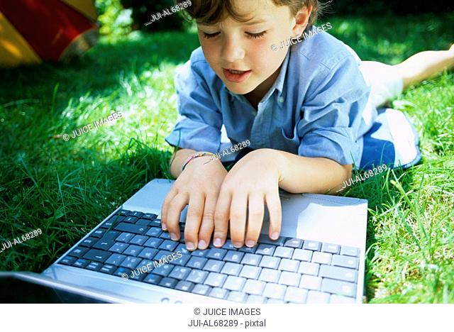 Boy lying on the grass with a laptop