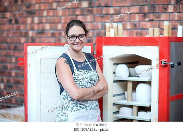 Portrait of female potter by workshop kiln