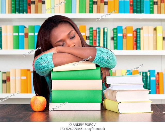 Tired female student, with hand on head sitting at classroom desk