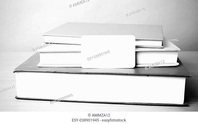 stack of book and business card on wood background black and white color tone style