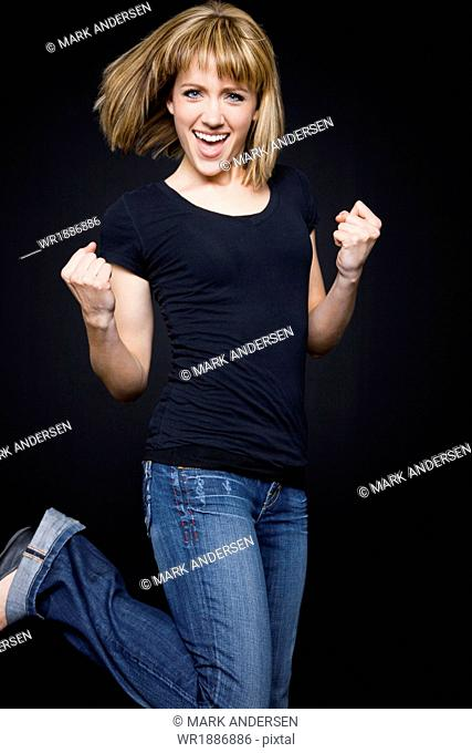 Studio shot of young woman cheering and making fists