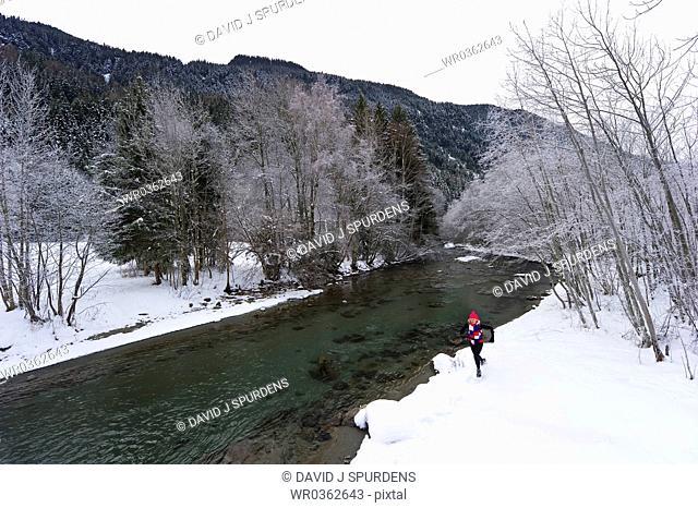 Women running alongside a snowy river