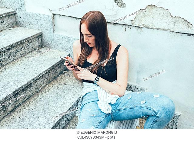 Young woman sitting on stairway reading smartphone texts