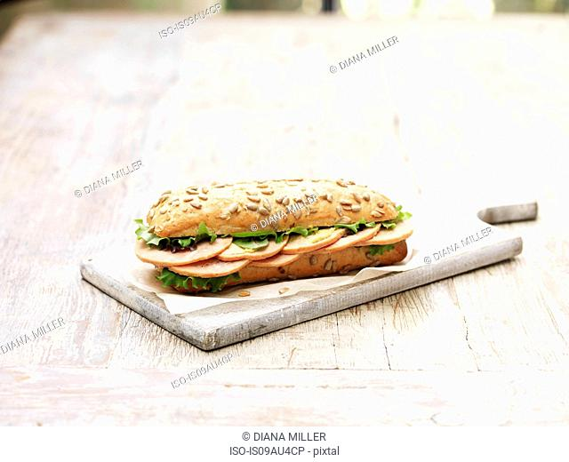 Sliced honey cured ham with salad leaves in seeded bun