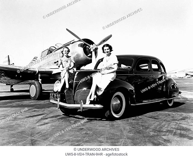 California: 1939 Two women sit on the fenders of a 1939 Lincoln Zephyr sedan at an airport with a single engine plane parked behind them