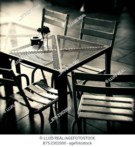 Metal chairs and table with an ashtray and a flower on a terrace of a bar in Plaza Real, Catalonia, Spain, Europe