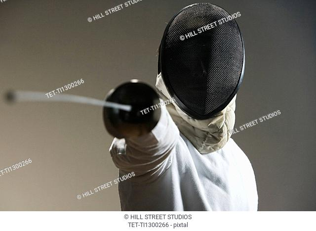 Close up of fencer in mask pointing fencing foil