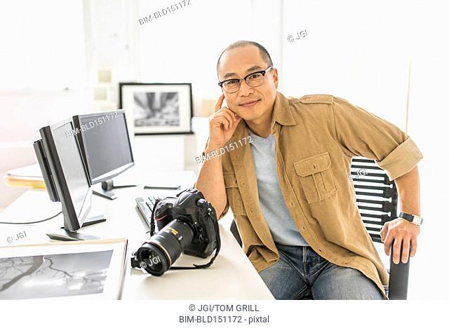Korean photographer smiling at desk