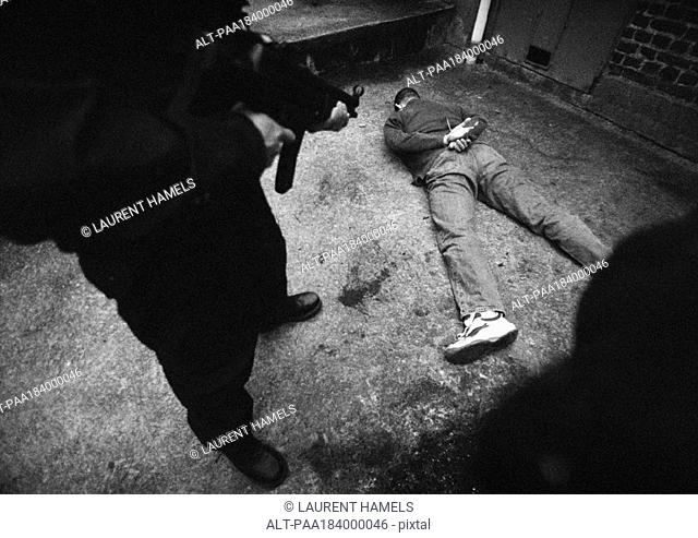 Man standing and pointing sub-machine gun at man face-down on floor, b&w