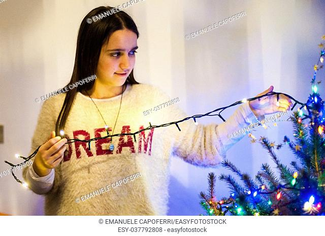 girl at home while decorating Christmas tree