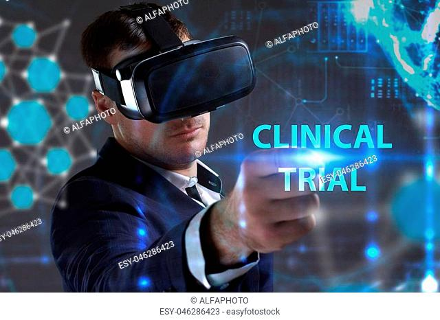 Business, Technology, Internet and network concept. Young businessman working in virtual reality glasses sees the inscription: Clinical trial