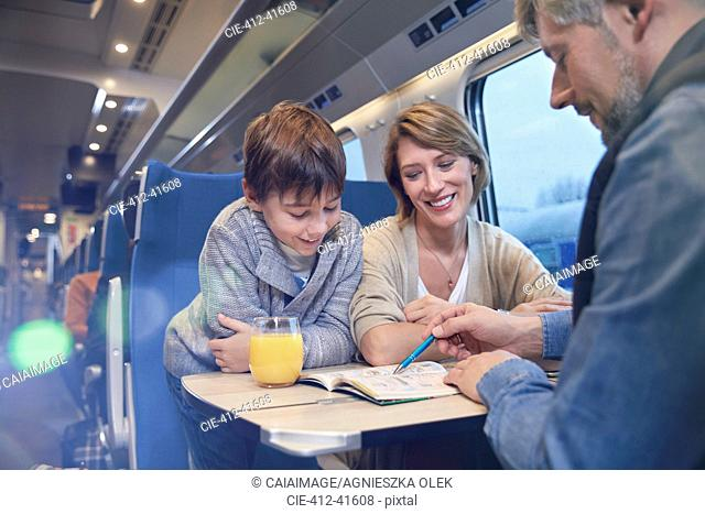 Family looking at travel guidebook on passenger train