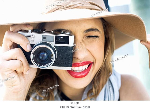 Close up of glamorous young woman holding up film camera