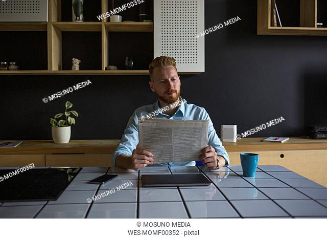 Businessman reading newspaper at home