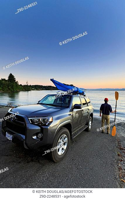 Man getting ready to go sea kayaking, Nanaimo, Vancouver Island, British Columbia