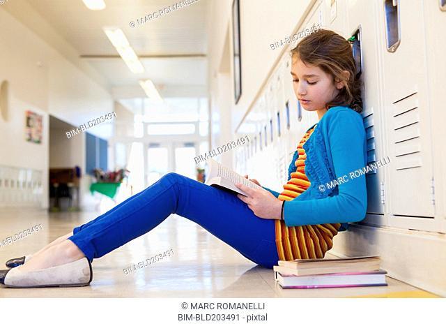 Caucasian student reading in school hallway