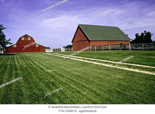 Two Red barns down gravel drive lined with wooden post fence midwest, USA
