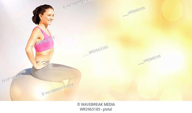 Smiling woman sitting on yoga ball