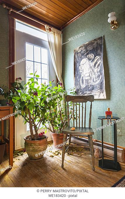 Antique wooden chair and green plants in terracotta planters in guest bedroom inside an old 1927 American Four Squares house, Quebec, Canada