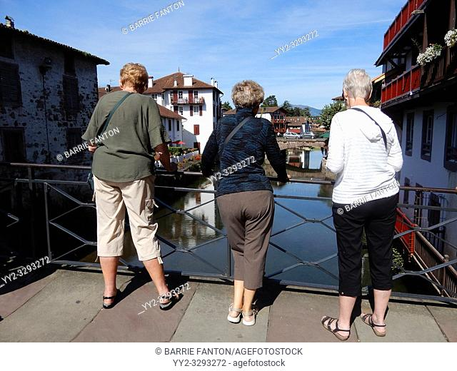 Three Female Tourists Gazing at River Nive, Saint-Jean-Pied-de-Port, France