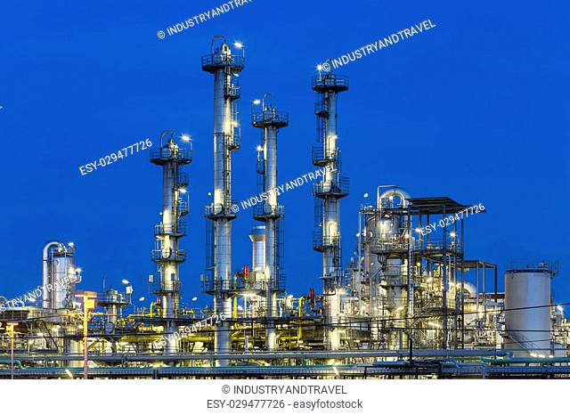 Detail of four distillation towers in a chemical plant and refinery with night blue sky
