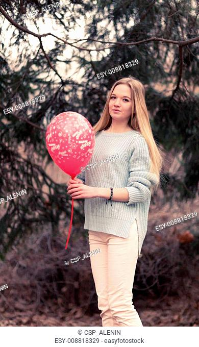 Open portrait of the young woman the beautiful woman in cold weather in park. The sensual blonde poses and is cheerful with a red balloon