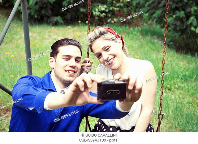 Young vintage couple taking selfie camera in garden
