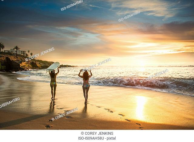 Surfers carrying surf board, walking along beach