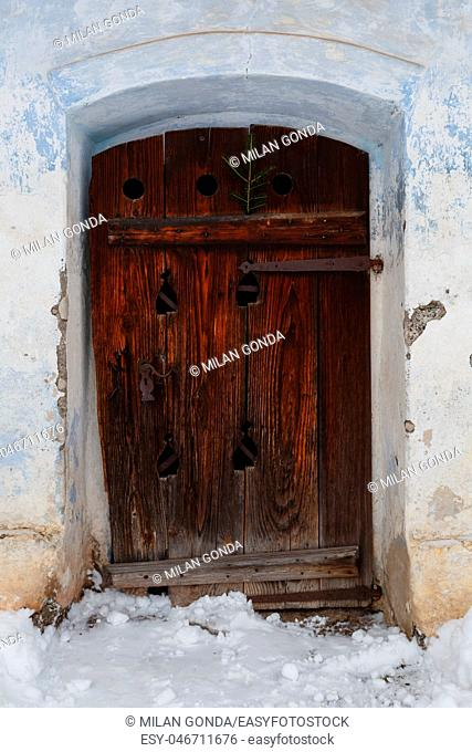Carved wooden door of a traditional granary with Christmas decoration in Bela-Dulice village, northern Slovakia