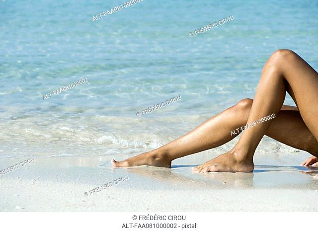 Woman's legs on beach, low section