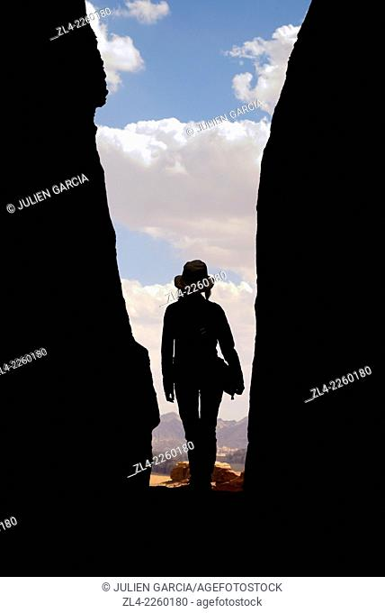 Silhouette of a woman with a hat in a narrow canyon. Jordan, Wadi Rum desert, protected area inscribed on UNESCO World Heritage list. Model Released