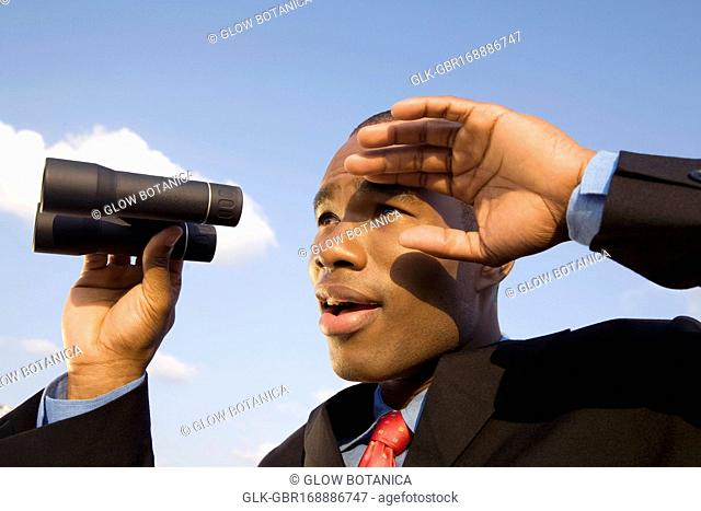 Close-up of a businessman holding binoculars and looking surprised