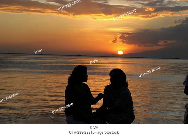 Women on Roxas Boulevard watching the sun setting, Metro Manila, Philippines
