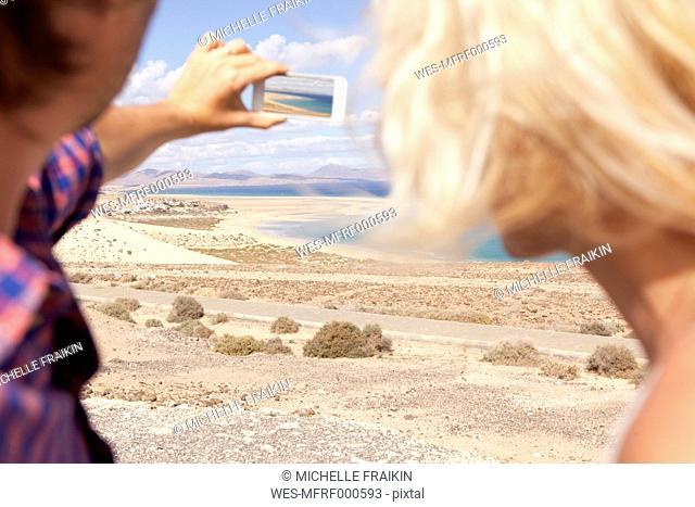 Spain, Fuerteventura, Jandia, couple taking picture at the coast