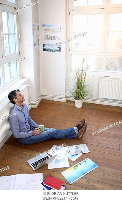 Man sitting on the floor in office