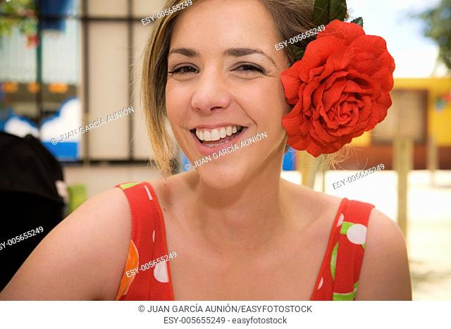 Young woman with gipsy dress and red flower on head at Cordoba Fairground, Spain